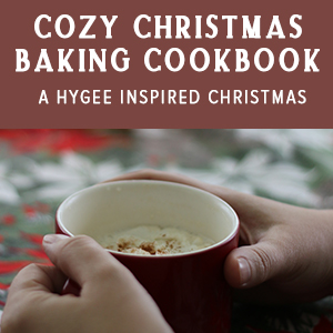 """a cup of coffee with a banner that says """"Cozy Christmas Baking Book: A Hygge-Inspired Christmas"""""""