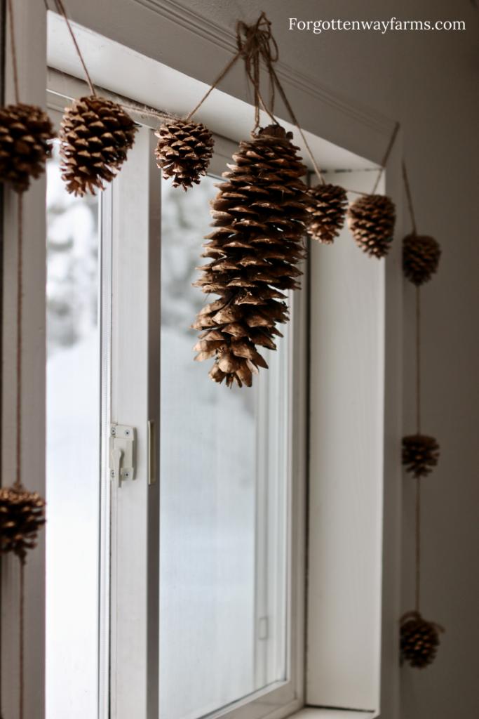 Golden pinecones strung over a window