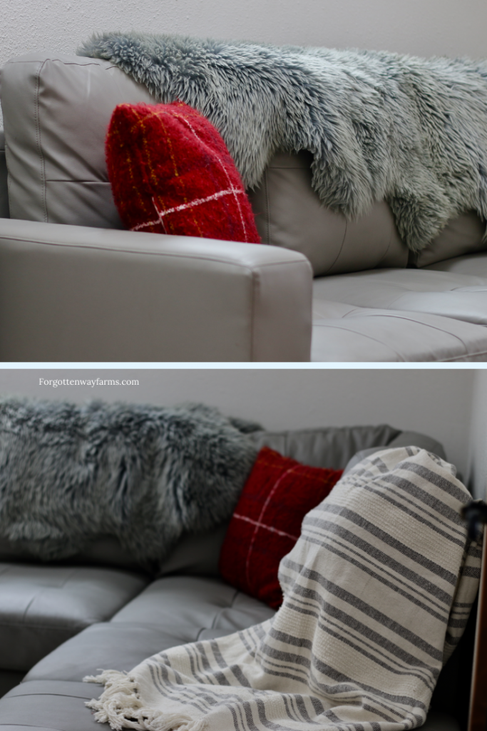 A grey couch, with grey fur draped over it and red flannel pillows.