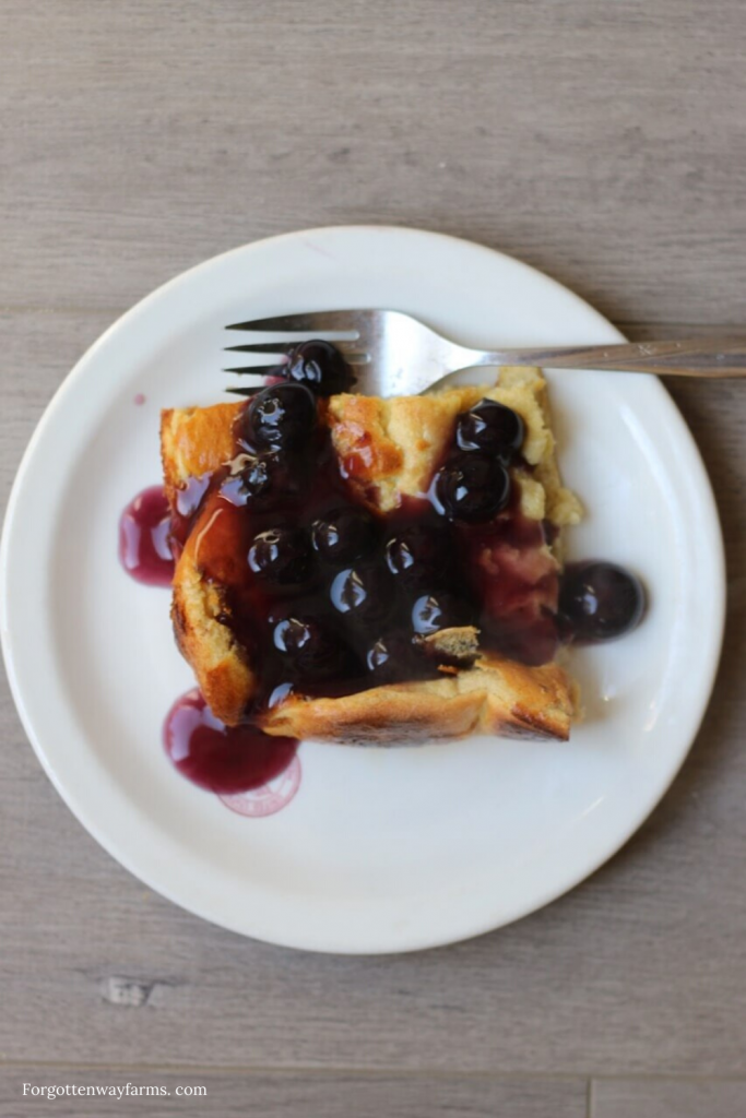 A plate of breakfast food, with blueberry syrup.