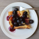 A plate with a serving of Gluten-free Dutch Pancake on it, drizzled with blueberry syrup