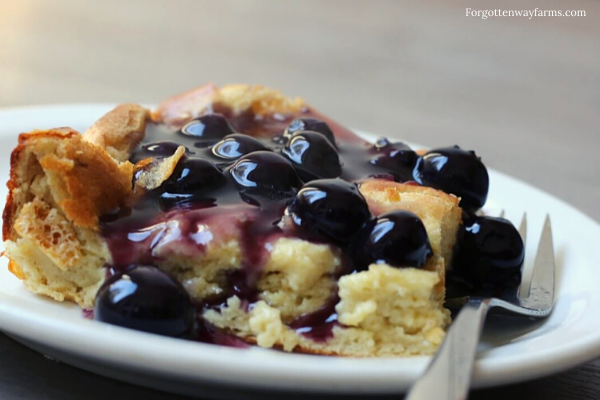 Gluten-free Dutch Baby coated in blueberry syrup.