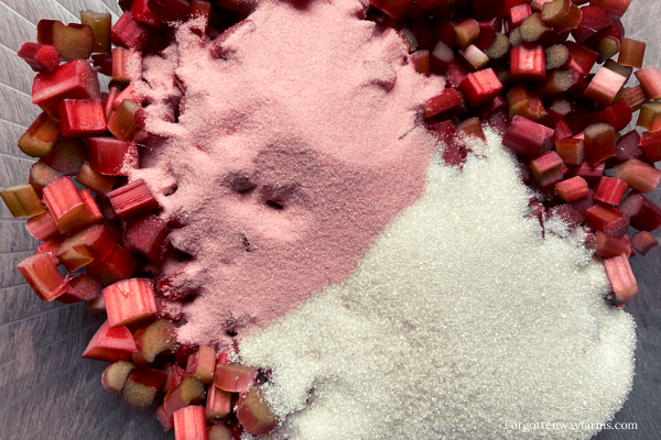 Freshly chopped rhubarb in a bowl with sugar and strawberry jello.