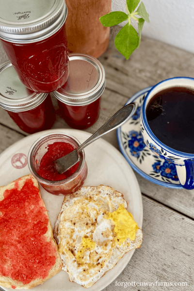 Preserves spread on toast, with coffee on the side and three jars of preserves.