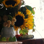 A bouquet of sunflowers and hops on the mantle