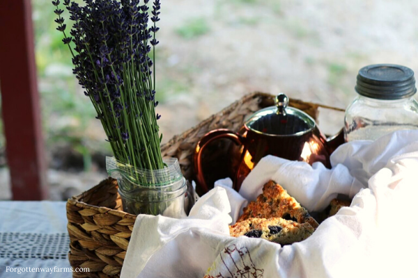 A hamper basket filled with scones, dried lavender bouquet, and a tea pot.