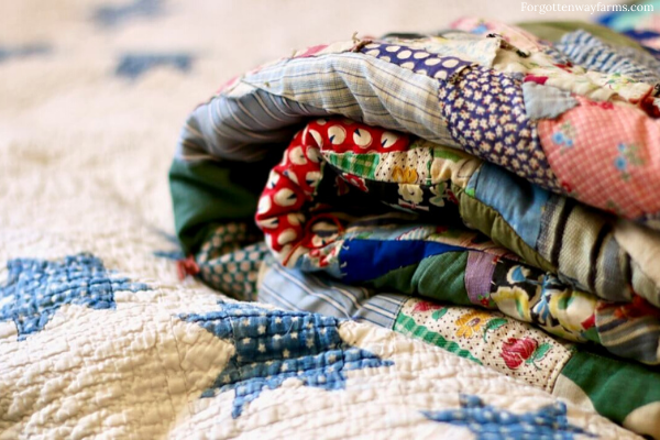 A stack of worn, but cozy quilts.